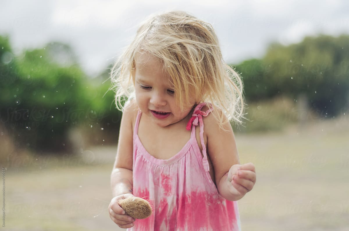 Little girl getting wet in the rain by Dominique Chapman - Stocksy United
