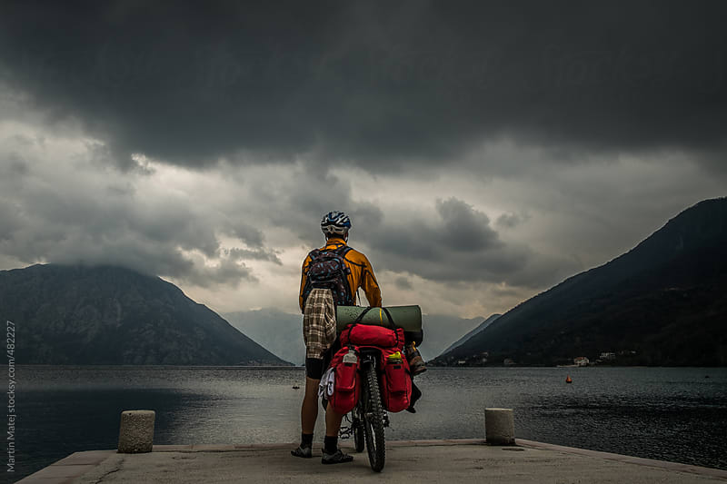 Young cyclist awaiting new adventures behind the dark clouds by Martin Matej for Stocksy United