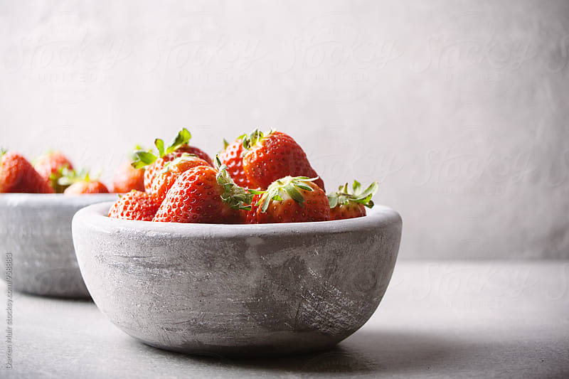 Strawberry's in concrete bowls in a concrete background. by Darren Muir for Stocksy United