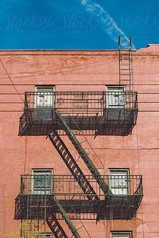 Fire escape and walkup apartment building in Harlem (NYC) by Lauren Naefe for Stocksy United