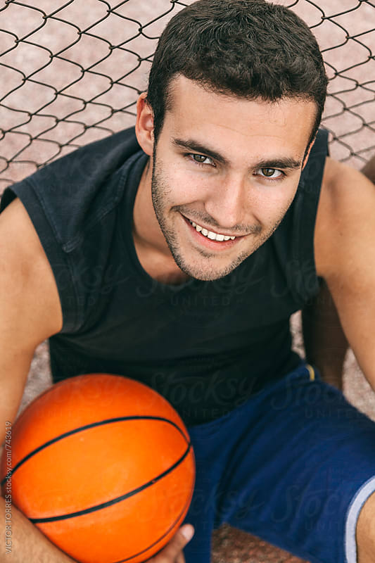 Young Happy Man Holding a Basketball Ball by Victor Torres for Stocksy United