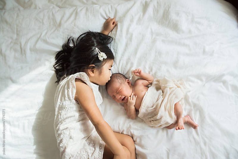 Asian siblings - BIg sister kissing her newborn baby sister by yuko hirao for Stocksy United