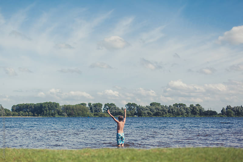A boy in swim shorts standing in a lake with his hands up on a summer day by Cindy Prins for Stocksy United