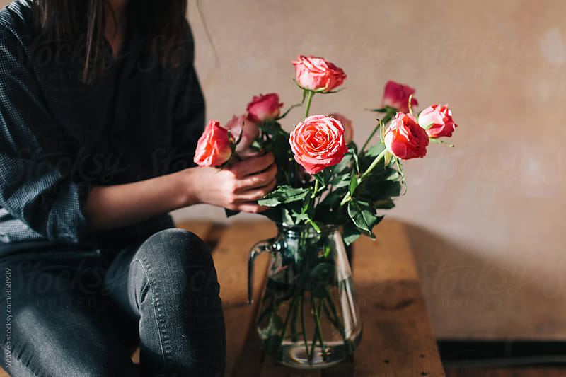 Woman arranging a bouquet of roses indoor by Marija Mandic for Stocksy United
