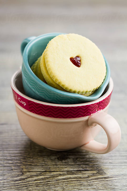 Jam biscuits in stacked measuring cups by Kirsty Begg for Stocksy United