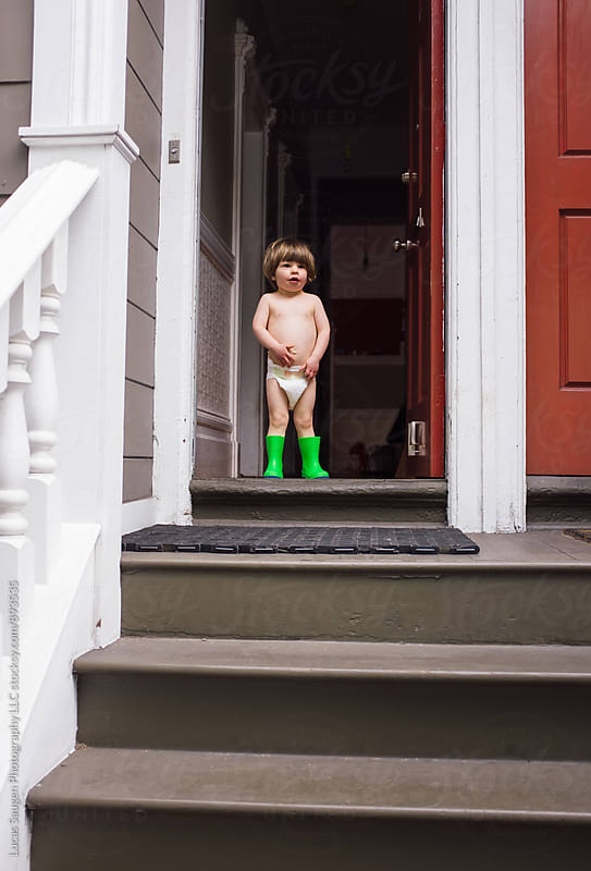 Young boy stands nearly naked on the front stoop by Lucas Saugen for Stocksy United