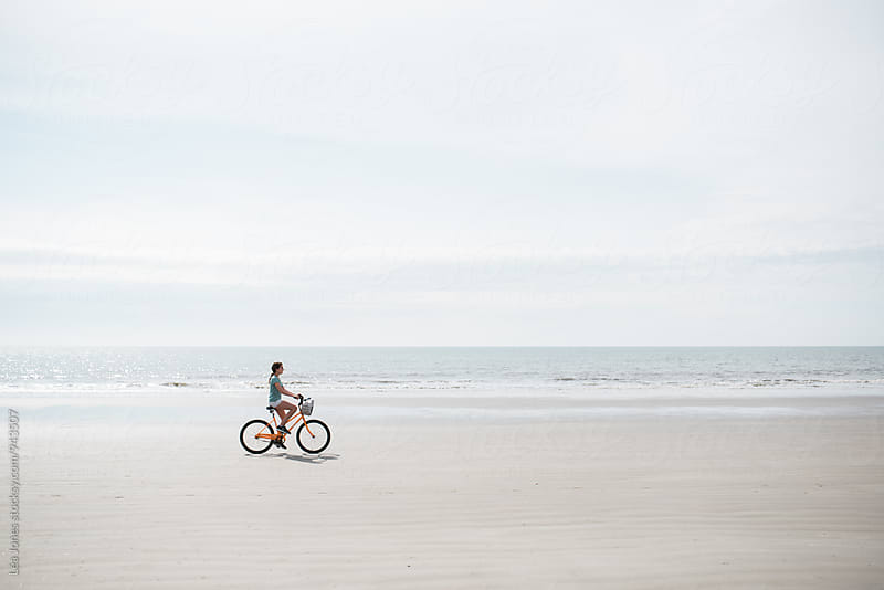 girl riding her bike on the beach by Léa Jones for Stocksy United