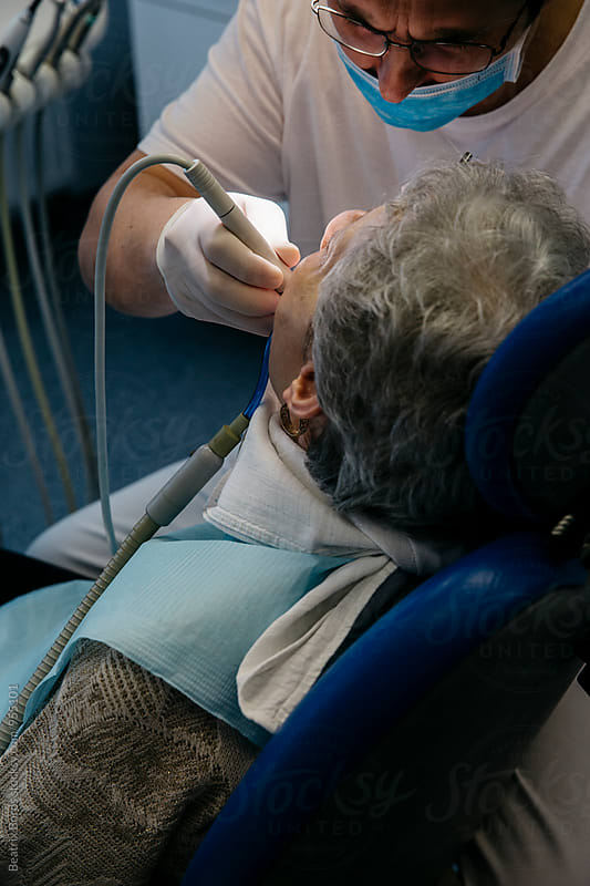 Senior woman at a dental clinic, dentist cleaning her teeth by Beatrix Boros for Stocksy United