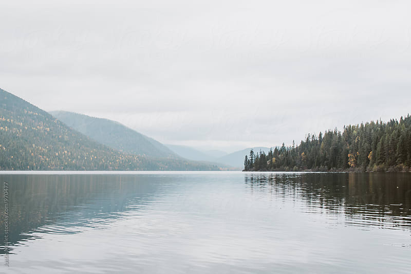Calm afternoon reflections on mountain lake by Justin Mullet for Stocksy United