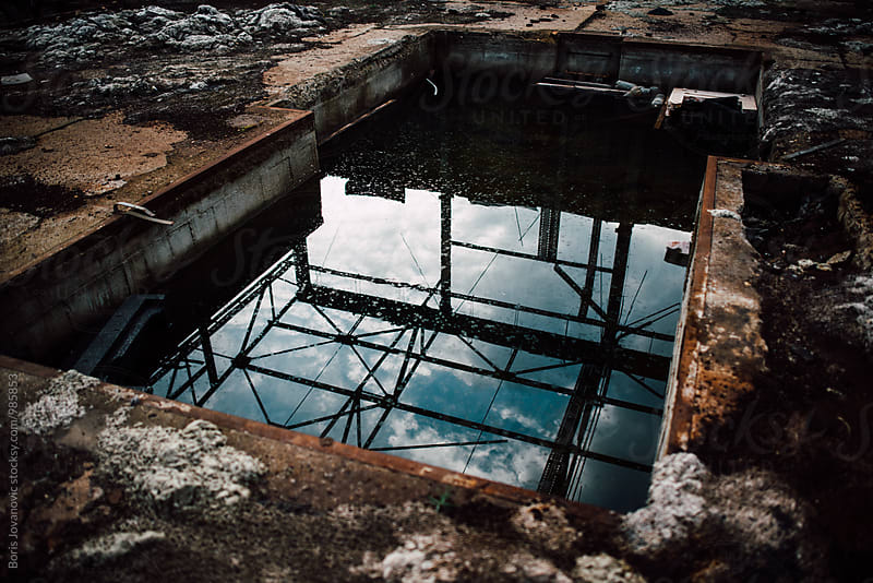 Sky and rooftop reflection in the abandoned factory pool  by Boris Jovanovic for Stocksy United