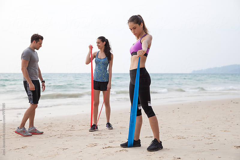 Two girlfriends exercising at the beach with a coach by Jovo Jovanovic for Stocksy United