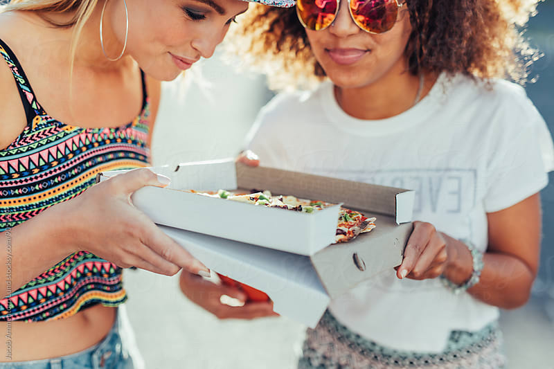 Two young girls holding a fresh and delicious pizza by Jacob Lund for Stocksy United