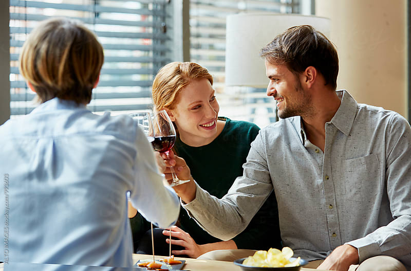 Happy Couple With Friend Having Lunch In Restaurant by ALTO IMAGES for Stocksy United