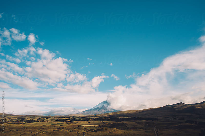 Smoking Volcano under Bright Blue Sky by Oscar Lopez for Stocksy United