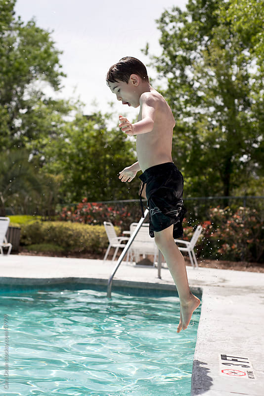 Boy jumps into a swimming pool while on vacation by Cara Dolan for Stocksy United