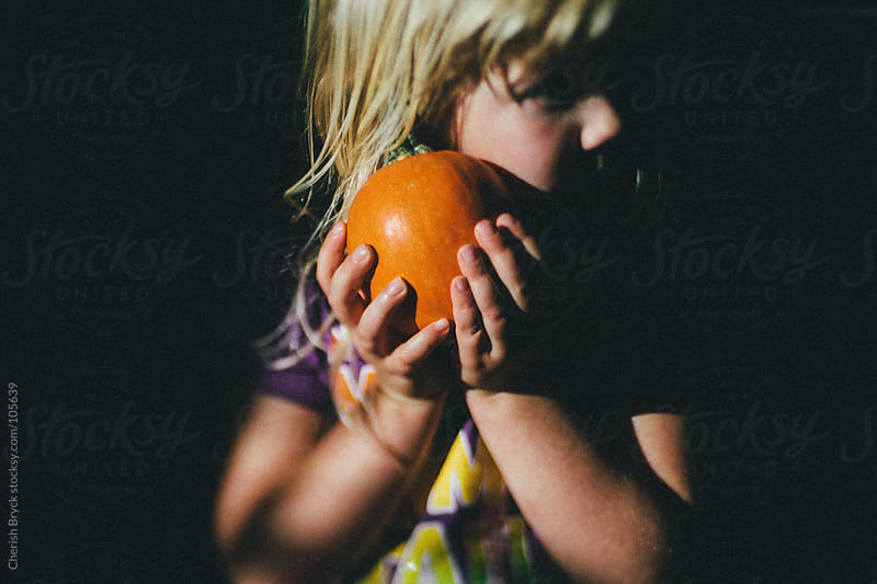 Little girl holds small pumpkin to her cheek. by Cherish Bryck for Stocksy United