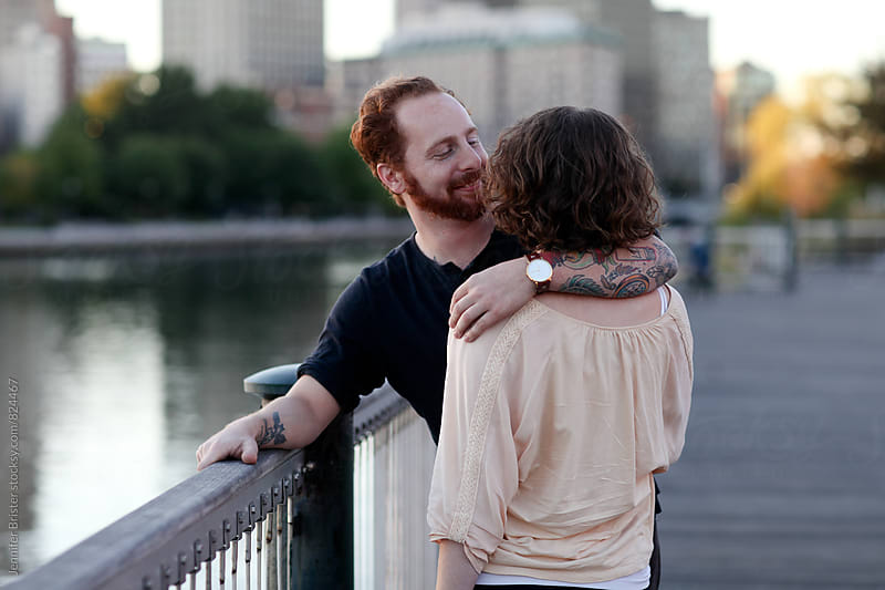 A couple talks and holds each other near river by Jen Brister for Stocksy United
