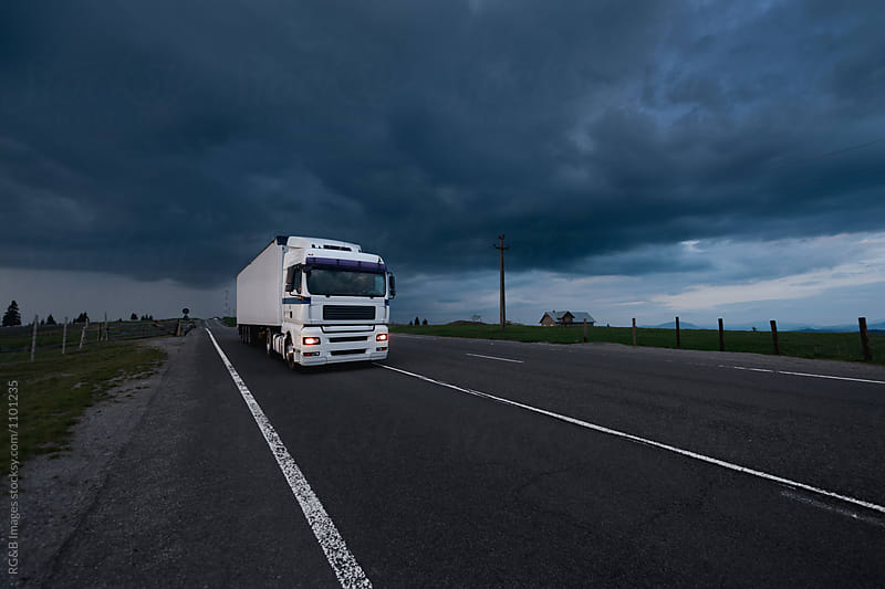Semitrailer truck driving on the road at night by RG&B Images for Stocksy United