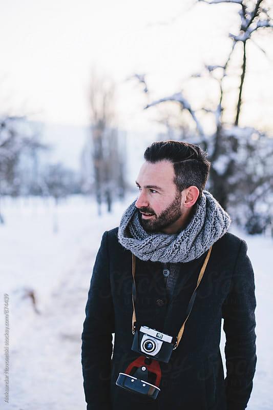 Hipster with film camera walking in the park by Aleksandar Novoselski for Stocksy United