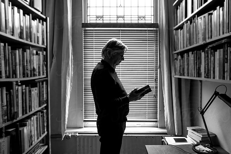 Senior man reading a book standing between bookshelfs by Ivo de Bruijn for Stocksy United
