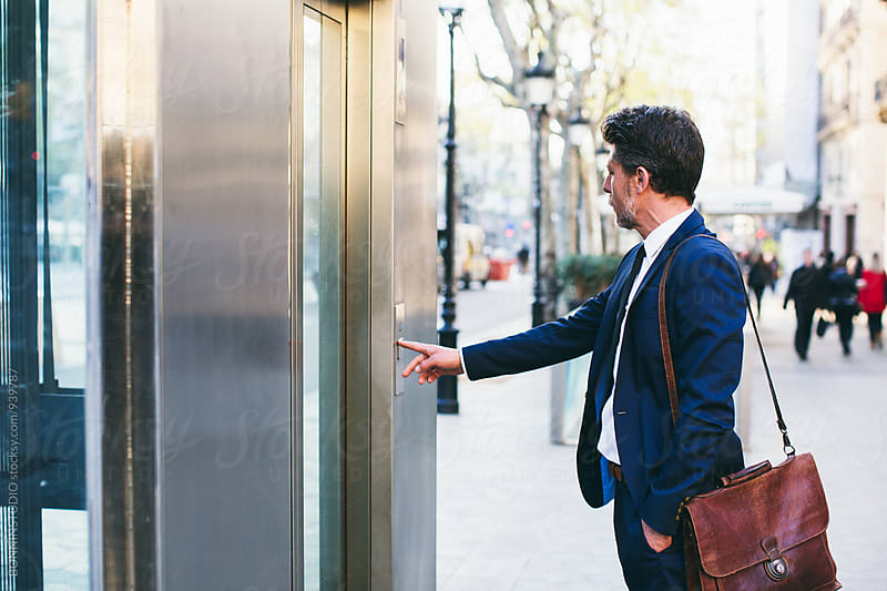 Mature businessman watching for the elevator on the street. by BONNINSTUDIO for Stocksy United