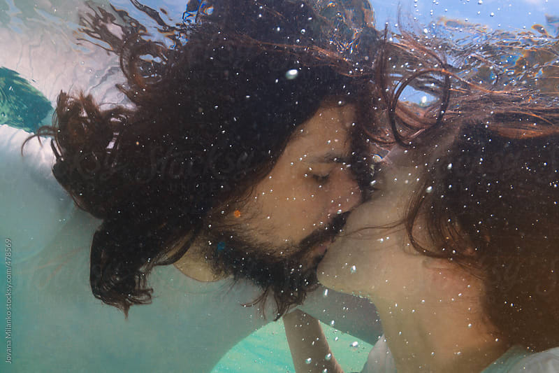 Couple kissing underwater by Jovana Milanko for Stocksy United