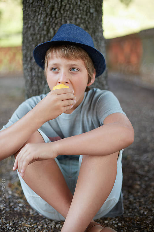 Young man eating fruit in the yard by Miquel Llonch for Stocksy United