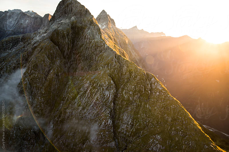 Sun flaring over huge mountains by Gary Parker for Stocksy United
