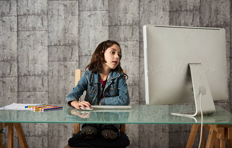 Little girl using computer at home by Guille Faingold for Stocksy United