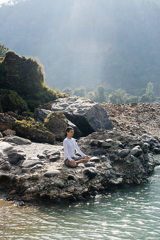 Man Sitting in Peace by the Holy Ganges River by Mosuno for Stocksy United