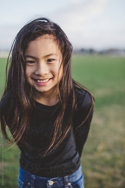 Cute elementary school aged asian girl happy in windy  field  by Rob and Julia Campbell for Stocksy United