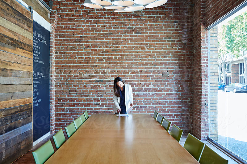 Millennial hispanic businesswoman in conference room by Trinette Reed for Stocksy United