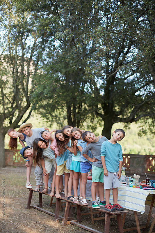 Portrait of ten children playing and posing on a bench at an outdoors party by Miquel Llonch for Stocksy United