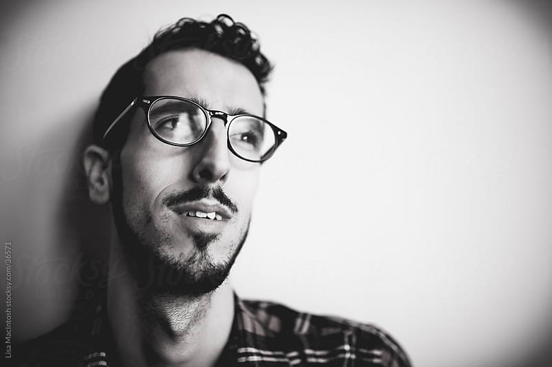 young bearded man with glasses and plaid shirt by Lisa MacIntosh for Stocksy United