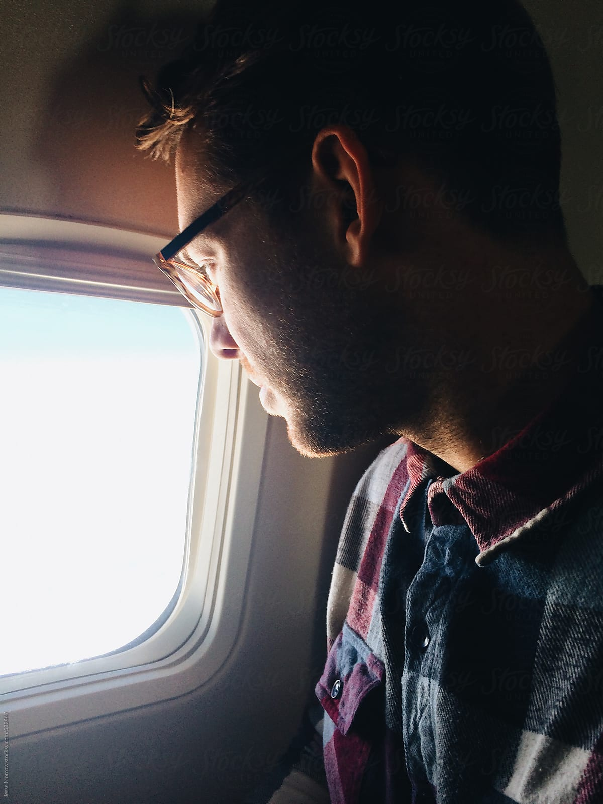 Young Man Looks Out Window In Airplane By Jesse Morrow Stocksy