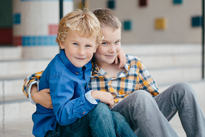 Two happy brothers sitting on the front steps of a school looking at camera by Ania Boniecka for Stocksy United
