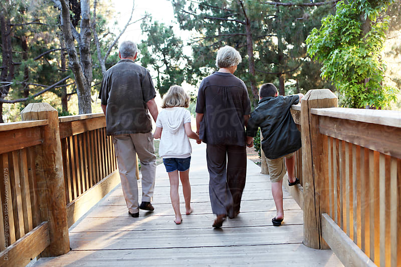 Grandparents walking across bridge with grand kids  by Dina Giangregorio for Stocksy United