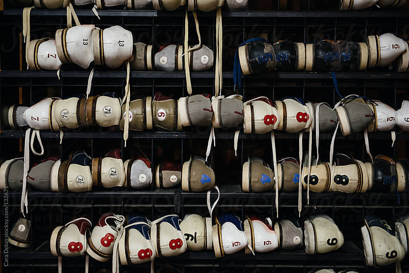 Rack filled with bowling shoes by Cara Dolan for Stocksy United