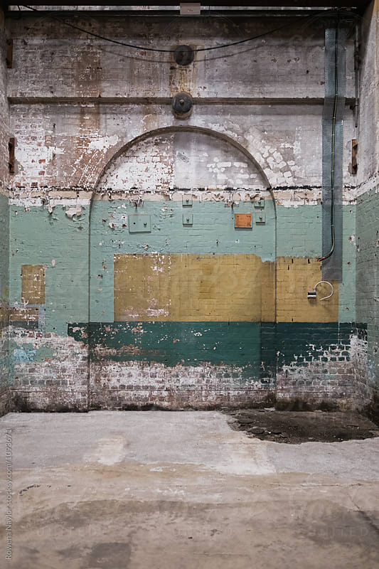 Old bricked up archways in delapidated warehosue by Rowena Naylor for Stocksy United
