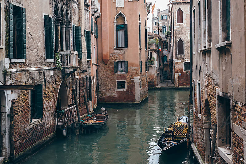 Brick houses with moored boats in Venice by Trent Lanz for Stocksy United