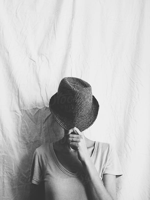 A woman hides her face behind a wool hat by Jacqui Miller for Stocksy United