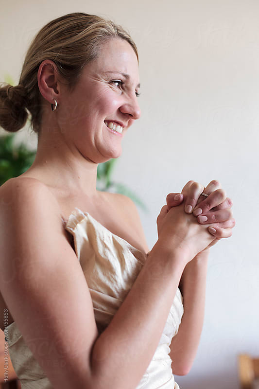 A smiling woman clasps her hands in front of her. by Holly Clark for Stocksy United