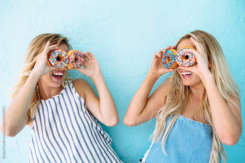 two friends with donuts for eyes by Brian Powell for Stocksy United