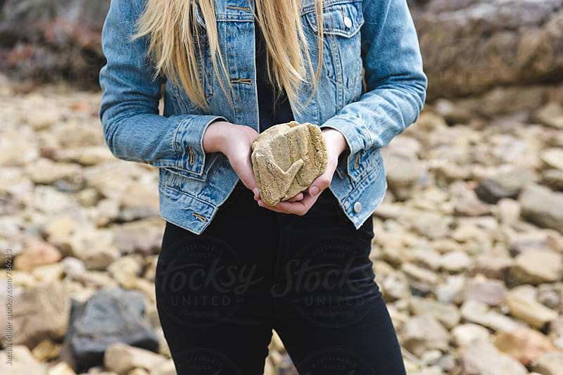 Fashionable young woman holding a found rock with an unusual heart shape by Jacqui Miller for Stocksy United