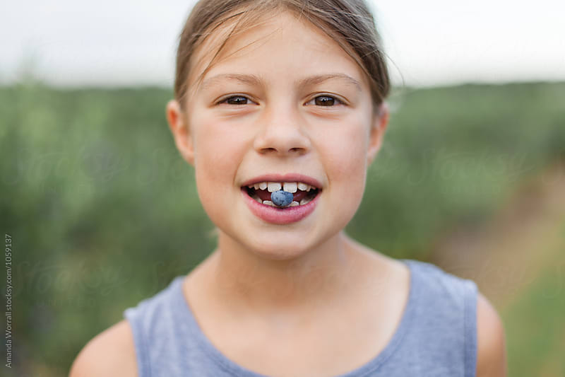 Girl holding a fresh picked blueberry in her teeth by Amanda Worrall for Stocksy United