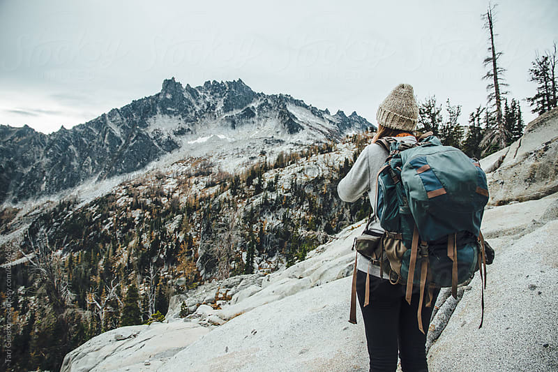 Backpacker looks out to Mountainous scenery by Tari Gunstone for Stocksy United
