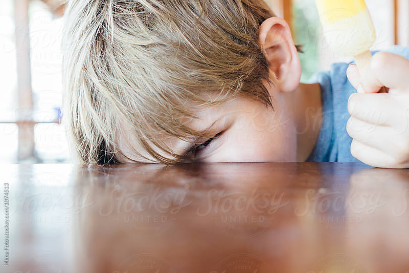 Boy twinkle above table by Mima Foto for Stocksy United