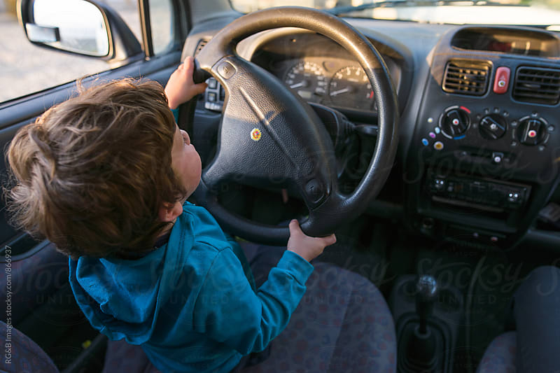 Little boy driving his father's car by RG&B Images for Stocksy United