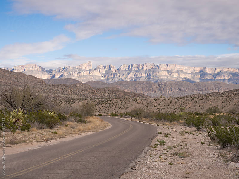 Desert road leading to mountains. Texas by Jeremy Pawlowski for Stocksy United