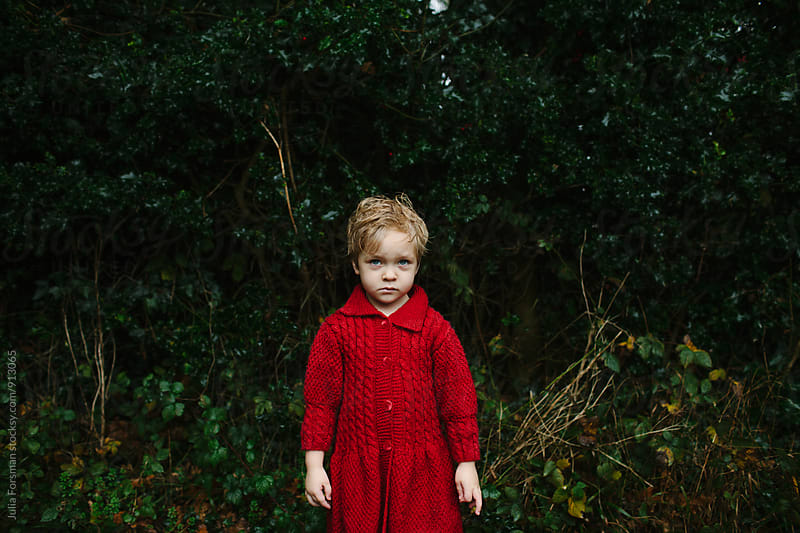 Grumpy child standing outside in the rain. by Julia Forsman for Stocksy United